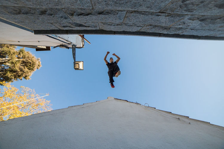 Young man doing impressive parkour jump from one roof to another. Athlete Athletic Freedom Freerunning Jump Lifestyle Man Parkour Roof Stunt Acrobat Action Active Challenge Danger Energy Extreme Sports Fit Fitness Impresive Jumping Leisure Activity Male Trick  Urban