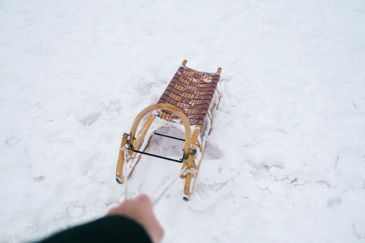 Snow Winter Cold Temperature Human Body Part Day Nature One Person High Angle View Human Hand Sled Outdoors Field Frozen Land Body Part White Color Holding Hand Extreme Weather Human Limb Blizzard
