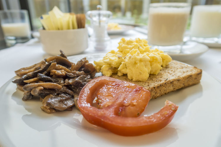 Healthy breakfast with tomato, mushroom and scrambled egg on a whole wheat bread Bread Break Close-up Coffee Day Food Food And Drink Freshness Fungi Indoors  Milk Mushrooms No People Plate Pomodoro Ready-to-eat Scrambled Eggs Table Tomato Whole Wheat Bread