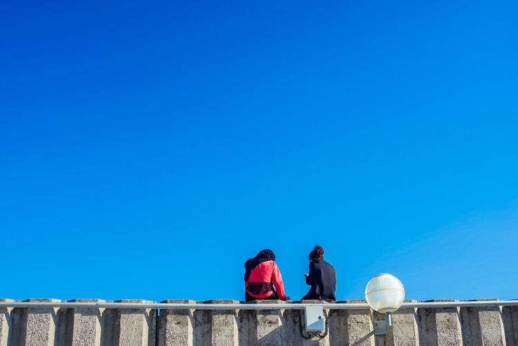 Rear view of friends sitting on retaining wall against blue sky