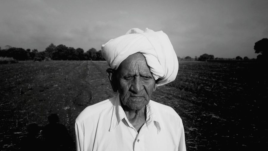 Close-up of senior man wearing turban standing on field against sky