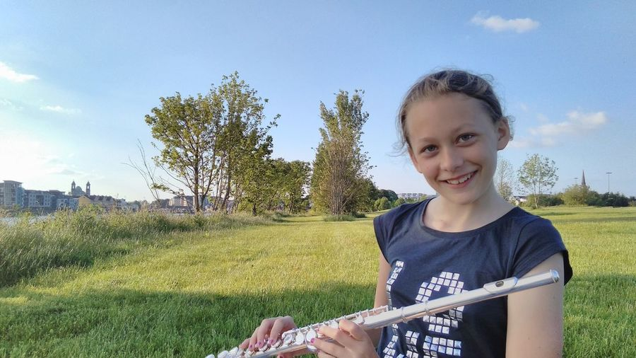 Portrait of smiling woman holding flute while standing on grassy field against sky