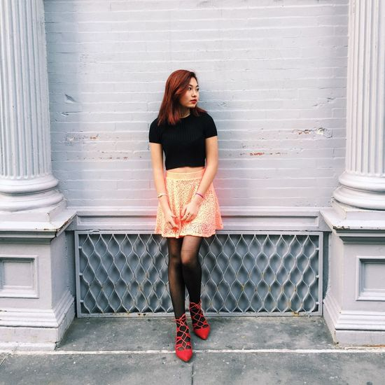 Full Length Of Beautiful Woman In Mini Skirt Standing Against White Wall