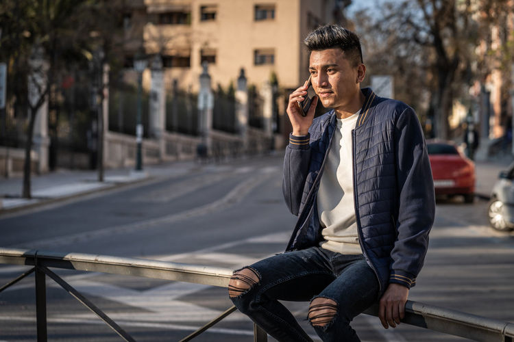 Young man using mobile phone while sitting in city