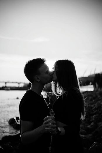 Side View Of Couple Standing Against Sky