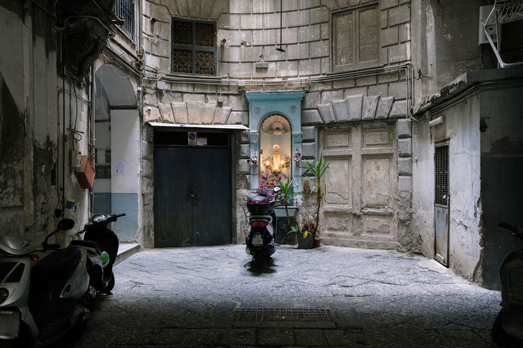 Scooters, Napoli - 2018 23mmf2 FUJIFILM X-T2 Madonna Napoli Scooter Architecture Belief Building Building Exterior Built Structure Burning Campania City Day First Eyeem Photo Fujifilm History Illuminated Italy Lighting Equipment Madonnina Nature No People Old Place Of Worship Religion Spirituality Street Streetphotography Capture Tomorrow My Best Photo Streetwise Photography The Photojournalist - 2019 EyeEm Awards