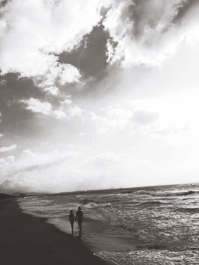 Silhouette people at beach against cloudy sky