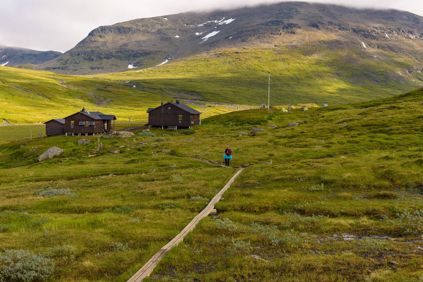 overnight cottages on the mountain Kungsleden Sweden Beauty In Nature Building Exterior Built Structure Day Field Grass Green Color Hemavan Hikers House Landscape Mountain Mountain Range Nature Outdoors Overnight Cabins Real People Scenics Sky Snow Tranquil Scene Tranquility