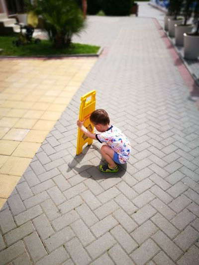 Boy Holding Information Sign On Footpath