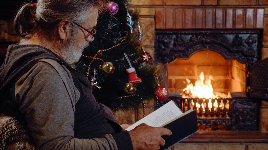 Man reading book while sitting by christmas tree at home
