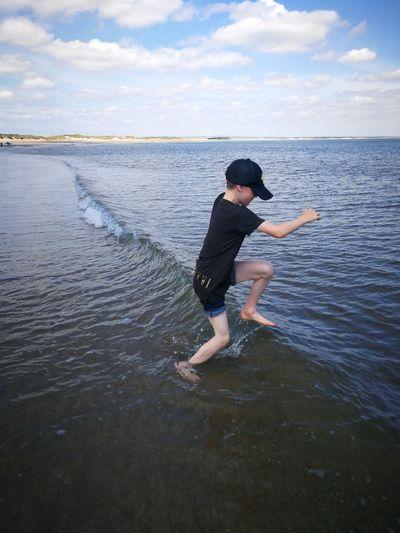 Full length of man in sea against sky