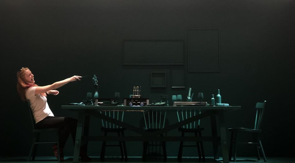 Woman laughing and gesturing while sitting on chair at dining table in darkroom