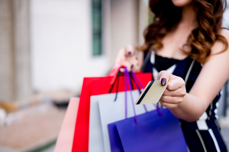 Midsection Of Woman Holding Shopping Bags And Credit Card In City