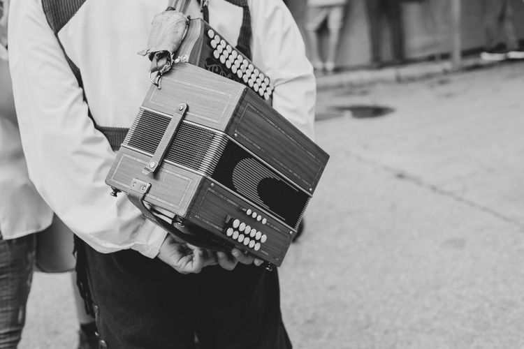 Midsection of man carrying accordion while standing on road