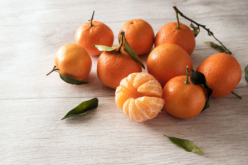 group of clementines with leaves, whole and peeled on a light gray wooden background with copy space Citrus  Copy Space Orange Clementine Day Food Food And Drink Fresh Freshness Fruit Gray Healthy Healthy Eating Juicy Leaves Manderine No People Orange Color Organic Peeled Ripe Still Life Tangerine Vibrant Color Vitamin