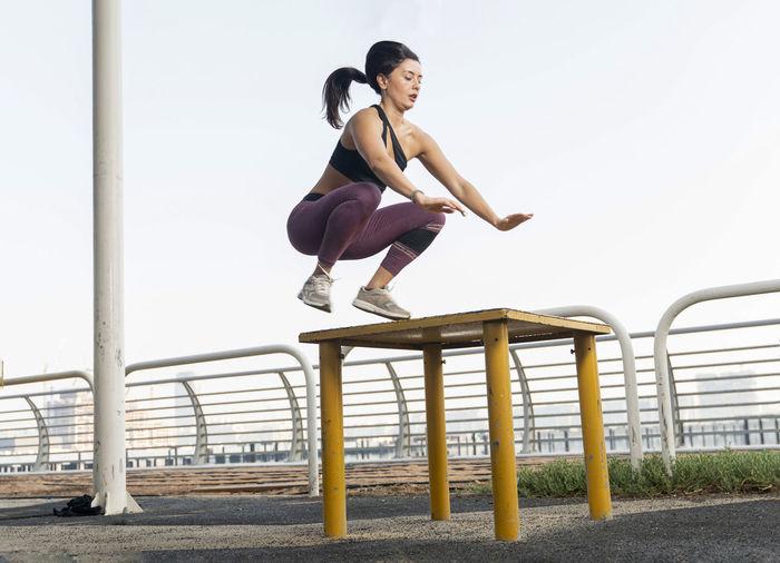 Full length of woman sitting on railing against sky