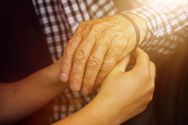 Cropped image of man putting bracelet on grandfather hand