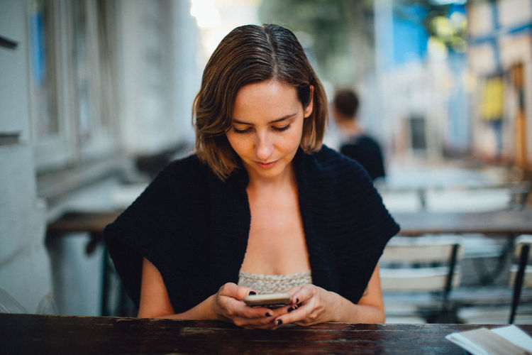 Woman using phone while sitting at outdoor cafe