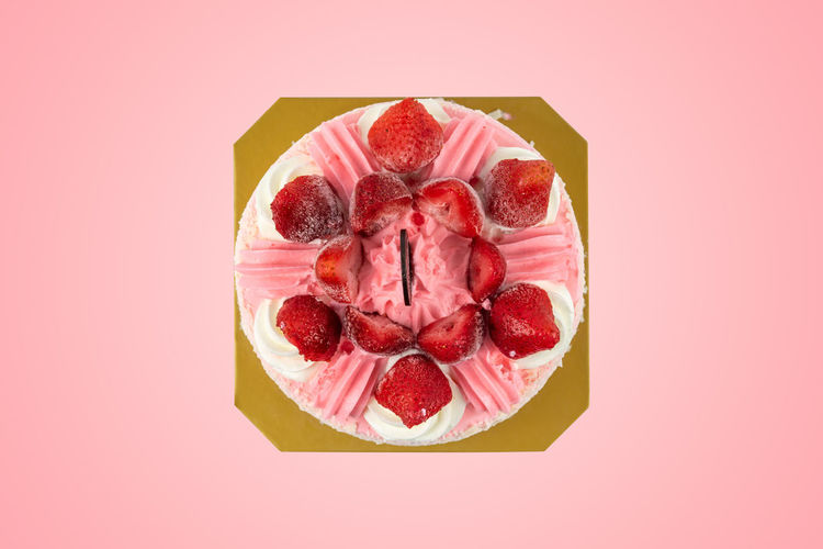 Directly above shot of strawberry cake against pink background