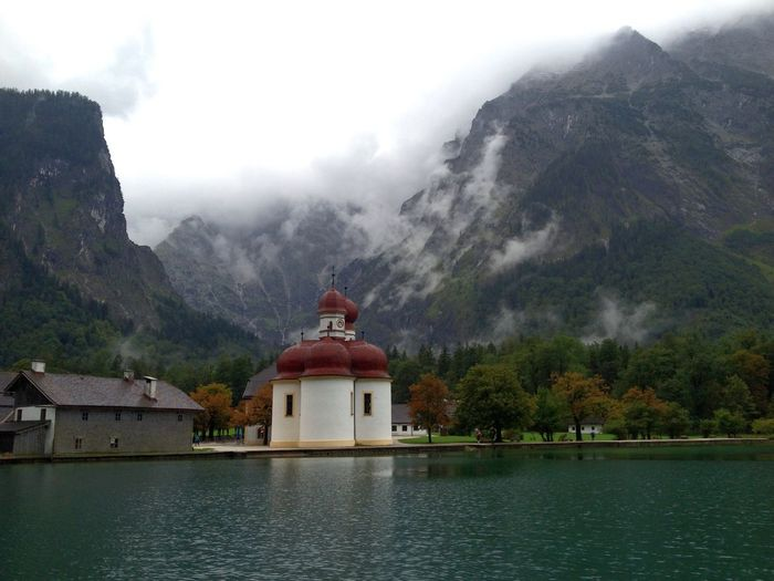 House and church at lakeshore against rocky mountains