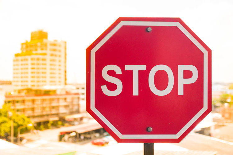 Close-up of stop sign in city against clear sky