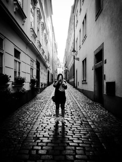 Selfies everywhere Blackandwhite Selfie ✌ Photographing Photo Architecture Built Structure Building Exterior Lifestyles One Person Full Length Walking City Cobblestone Footpath Alley Building The Street Photographer - 2018 EyeEm Awards