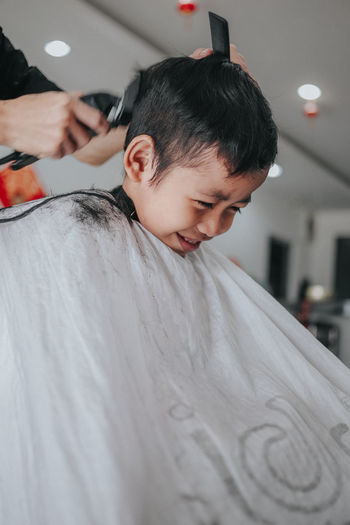 Cropped hand of person cutting boy hair at salon