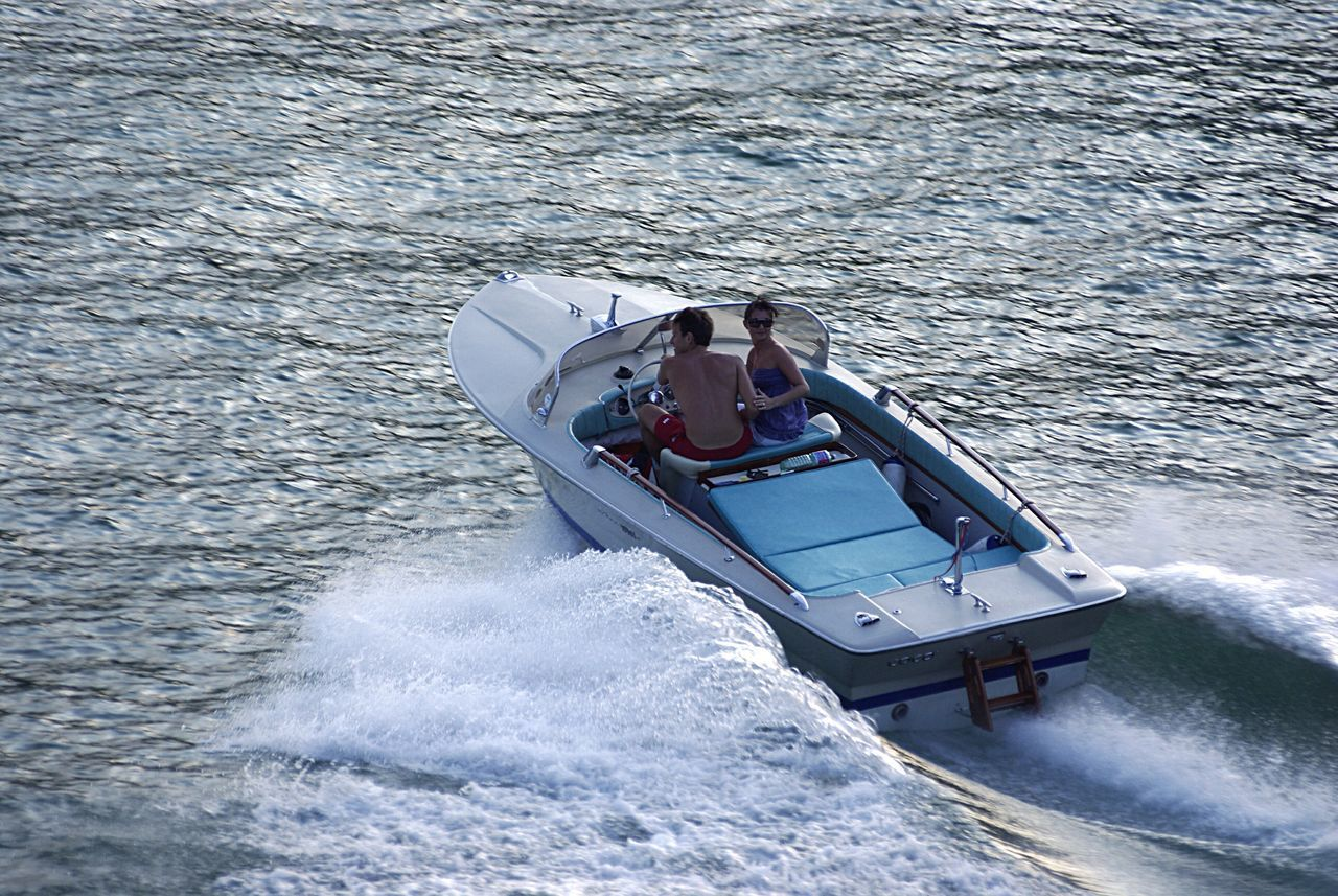 nautical vessel, transportation, high angle view, leisure activity, day, nature, motion, mode of transport, water, lifestyles, wake - water, outdoors, real people, sea, one person, men, wake, jet boat, people