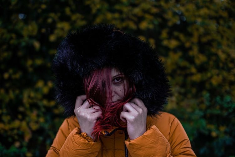 Portrait of young woman wearing warm clothing against plants