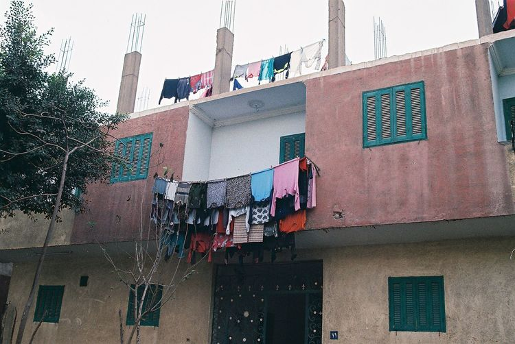 Film Travel Architecture Building Building Exterior Built Structure City Clothesline Clothing Day Drying Film Photography Hanging House Laundry Low Angle View Nature No People Outdoors Plant Residential District Sky Window