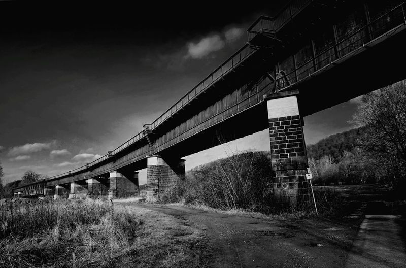 Low angle view of railway bridge against sky