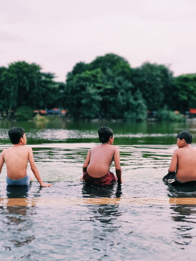 Rear view of boys sitting by lake