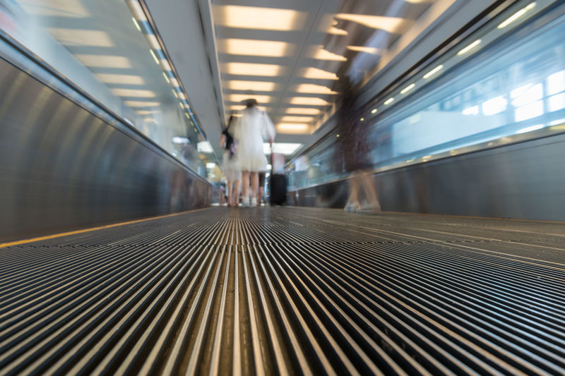 People on an escalator in motion. View from the ground up. Architecture Business City Transportation Travel Airport Blurred Motion Escalator Interior Lihgts Motion People Sky