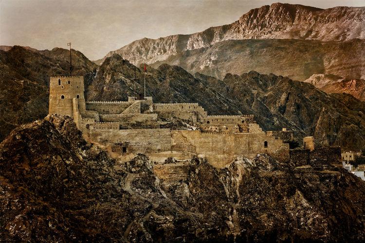 Castle against rocky mountains