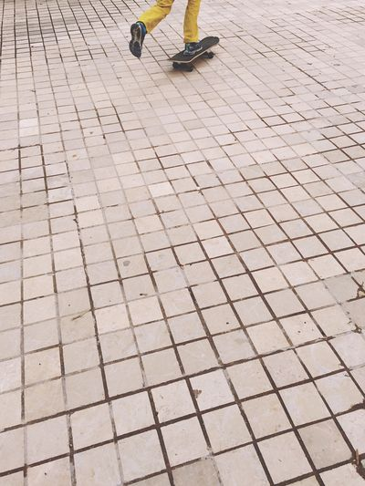 Low section of person skating on sidewalk