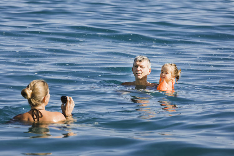 Cheerful family swimming in sea