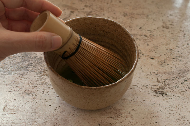 Cropped hand of holding mortar and pestle on table