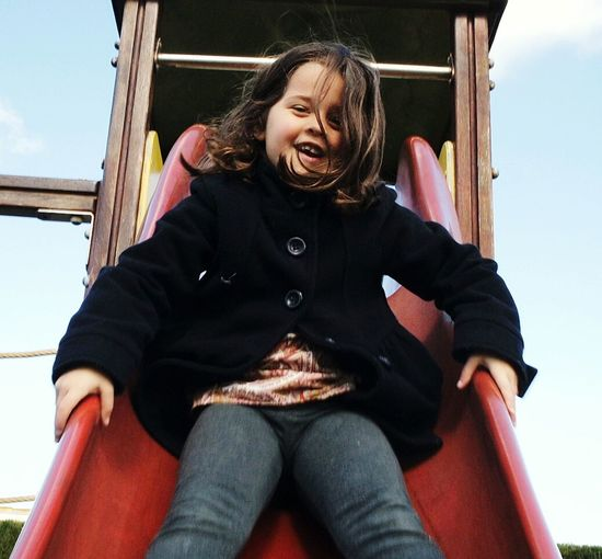 Low angle view of happy girl on slide in park