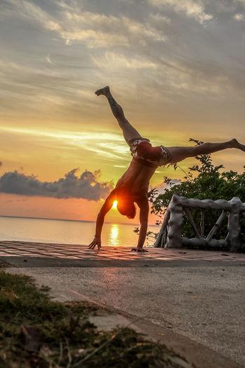 Man climbing on beach against sky during sunset