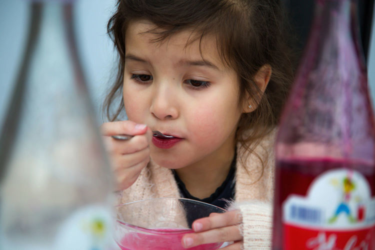 Close-up of girl drinking juice served in bowl