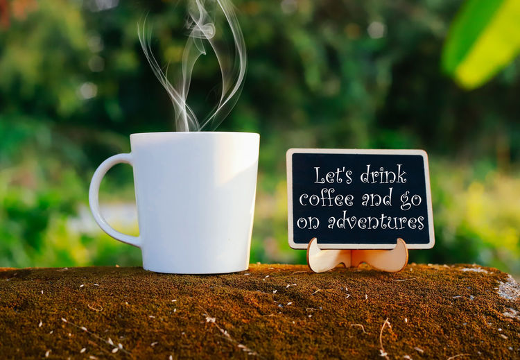 Let's drink coffee and go on adventures Cup Mug Text Communication Coffee Cup Food And Drink Western Script No People Drink Close-up Focus On Foreground Refreshment Plant Nature Coffee White Color Day Table Still Life Coffee - Drink Outdoors