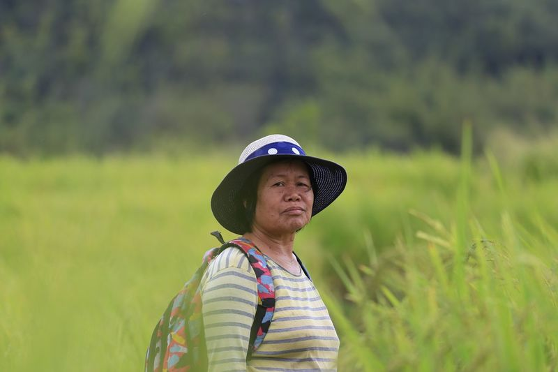 Portrait of mature backpack woman standing on field