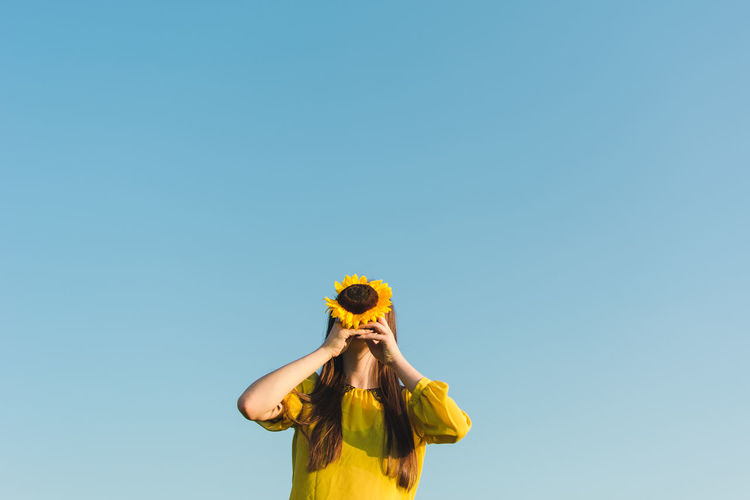 Low Angle View Of Woman Covering Face With Sunflower Against Clear Blue Sky