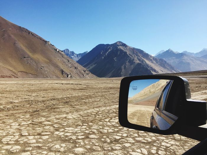 Driving on dry lake bed Andies Mountains Chile Embalse El Yeso Side-view Mirror Mountain Transportation Mountain Range Clear Sky Car Landscape Sand Day Sunlight Outdoors Land Vehicle Arid Climate Nature Scenics No People Blue Beauty In Nature Sky