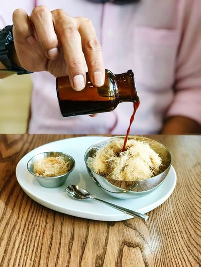 Midsection of man pouring syrup over dessert in bowl on table