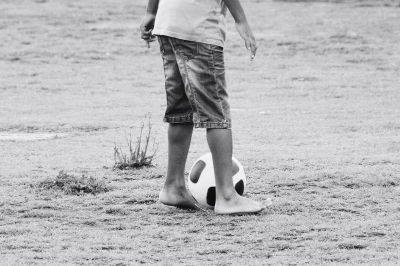 Low section of boy with soccer ball standing on field