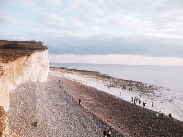 Chalk cliff by beach against cloudy sky