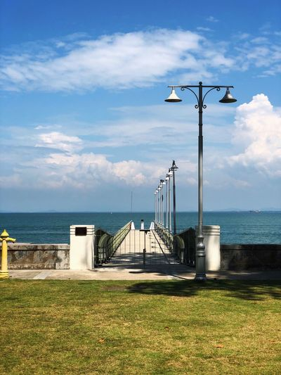Street light by sea against sky