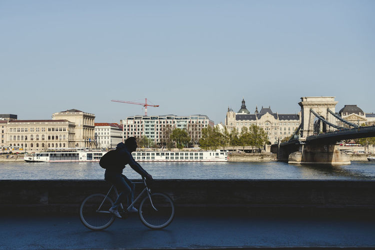 Cyclist silhouette in front of the Danube river and the The Széchenyi Chain photo. Architecture Bicycle Bridge Bridge - Man Made Structure Building Exterior Built Structure City Full Length Land Vehicle Lifestyles Mode Of Transportation One Person Outdoors Real People Riding River Sky Transportation Travel Water