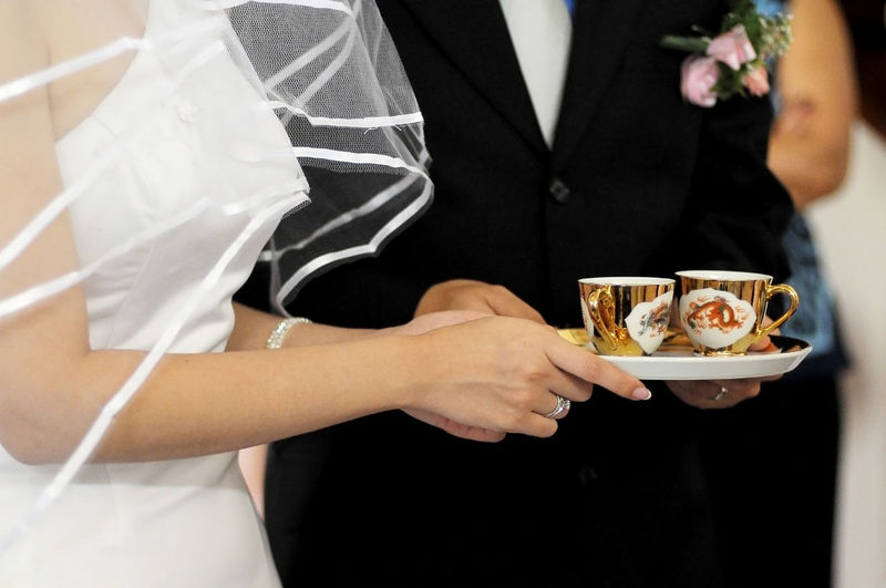 Midsection of wedding couple holding tea cups in plate